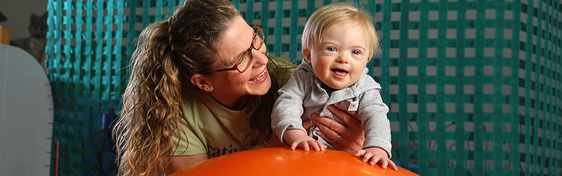 Infant with Down syndrome on large exercise ball with therapist