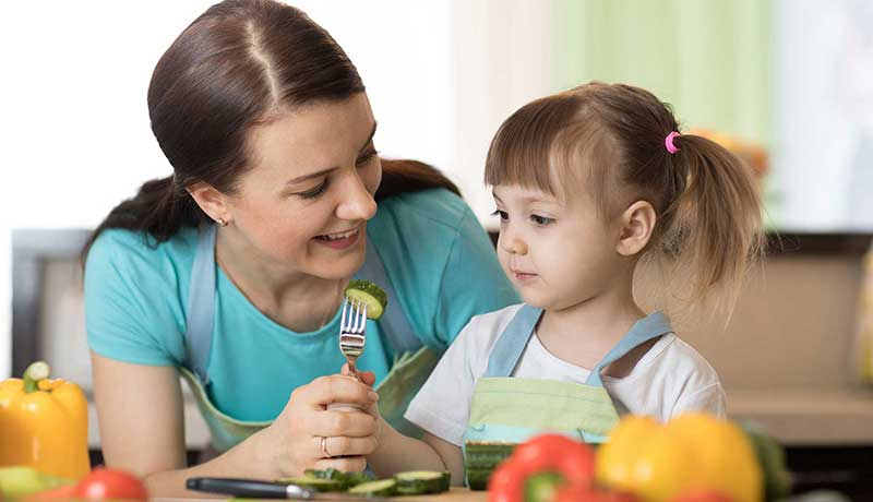 Mother holding fork with vegetable for young girl