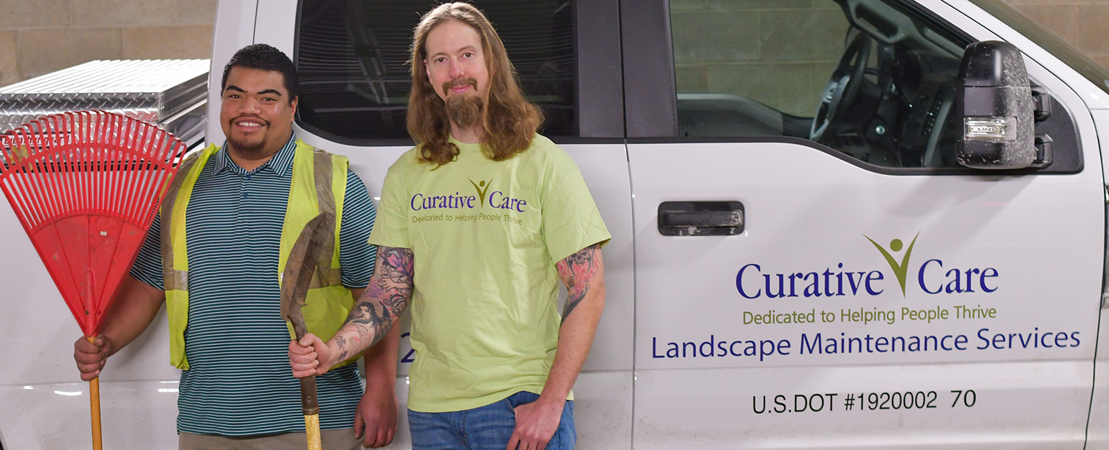 Adult client standing next to landscape supervisor, both holding lawn equipment