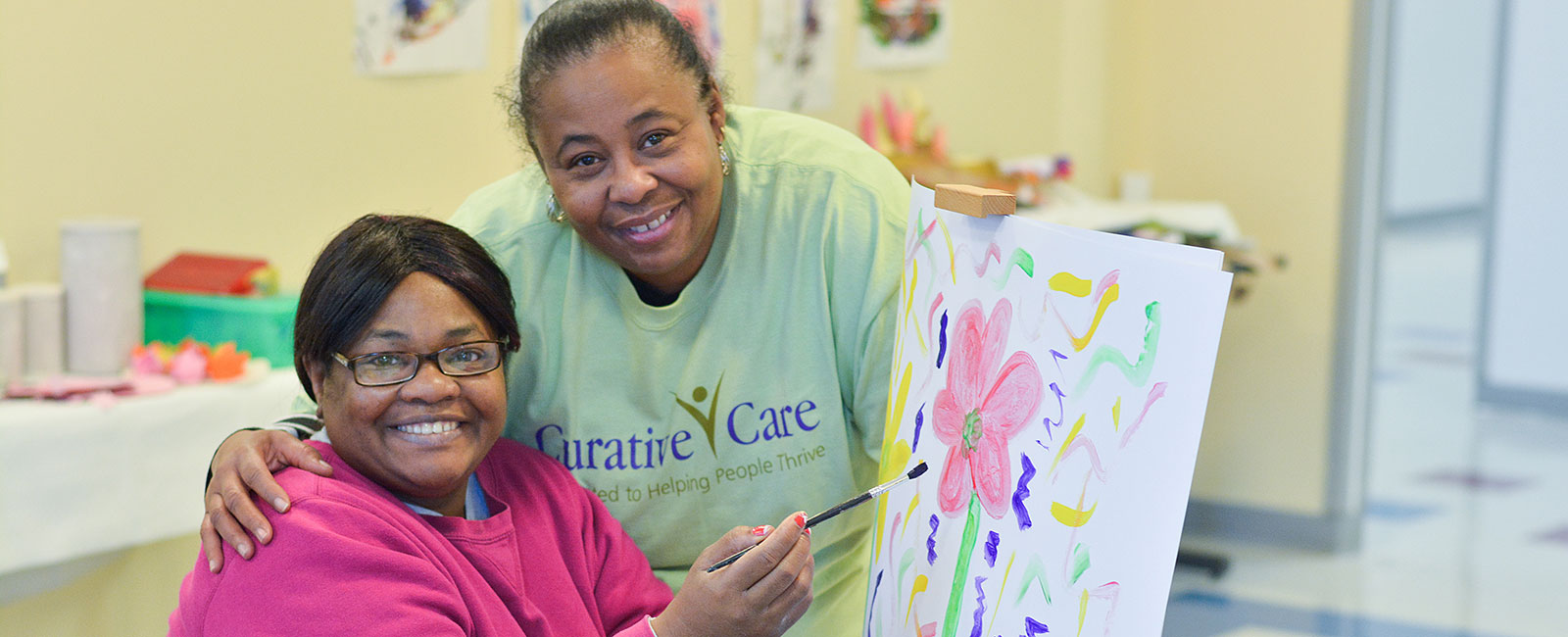 Adult female client painting a flower with employee caregiver